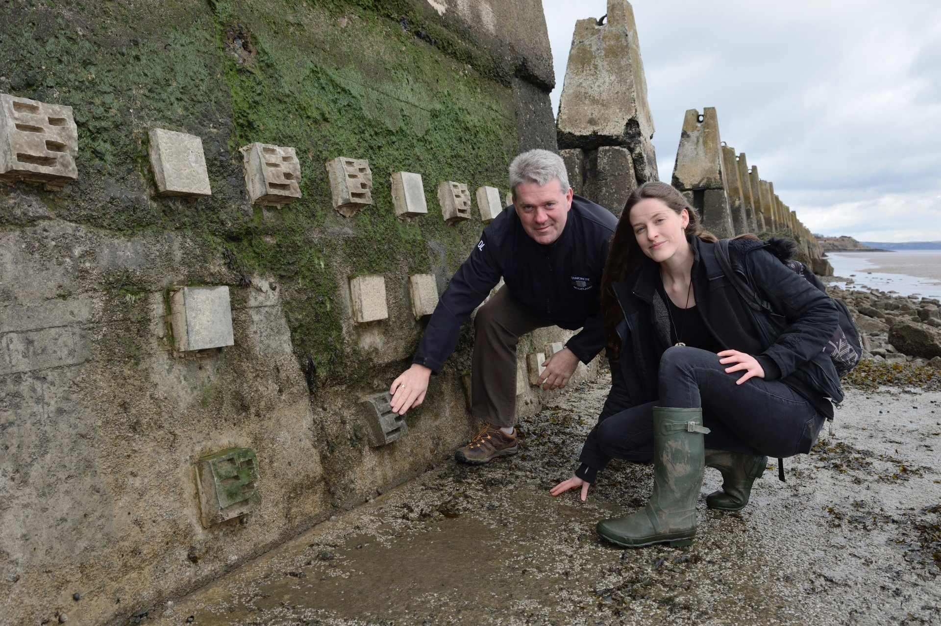 Dale Lyon Concrete in the Classroom) and Mairi MacArthur ( PhD student Glasgow Uni), standing beside some concrete habitat blocks installed on the sea defences at Cramond as part of the Concrete in the Classroom project. ©Lorne Gill/SNH