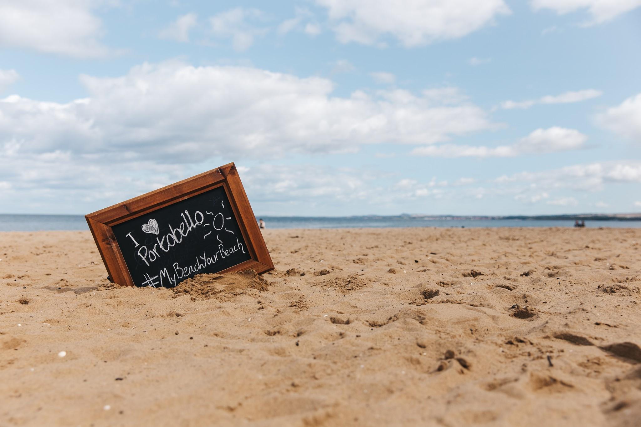 chalk board reading 'I love Portobello' on the beach